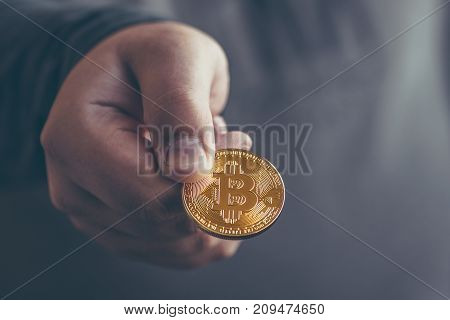 Cryptocurrency golden bitcoin coin in man hand - symbol of crypto currency - electronic virtual money for web banking and international network payment, selective focus, toned