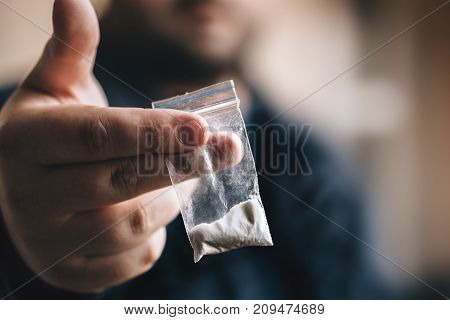 Drug dealer offers cocaine dose or another drugs in plastic bag, drug addiction on party concept, selective focus, toned