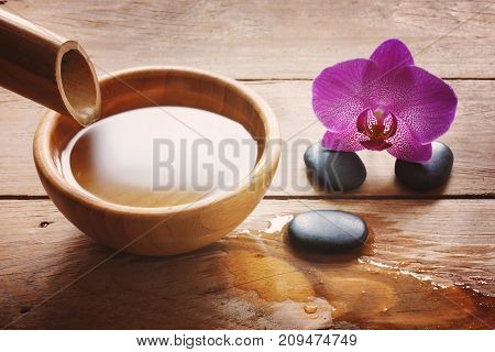 Composition On A Wooden Table With A Bamboo Stem And A Bowl Of Water, Stones For Spa Procedures And