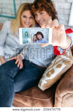 Top view of couple taking selfie on a sofa in a coffee shop. Selective focus on mobile in the foreground