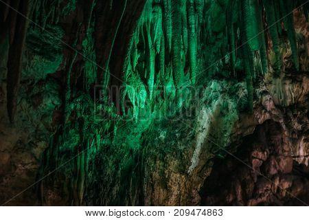 Beautiful illuminated limestone stalactites in Adygeya underground cave, speleology grotto concept