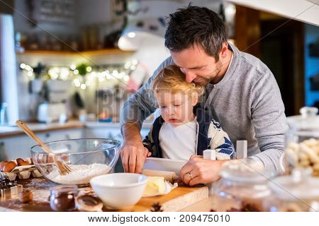 Man and toddler boy making cookies at home. Father and son baking gingerbread Christmas cookies.