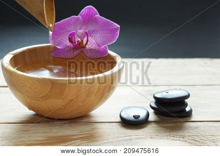 Bowl, Which Pours Transparent Water From The Bamboo, Orchid Flowers And Stones For A Hot Massage On