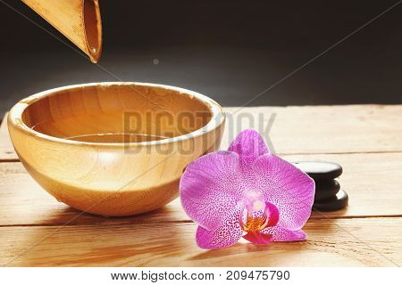 Bowl, Which Pours Water From The Bamboo Stem, Orchid Flowers And Stones For A Hot Massage On A Woode