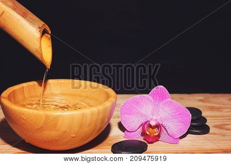 The Jet Of Water Is Poured From The Bamboo Into A Bowl On A Wooden Table, Next To The Spa Treatment
