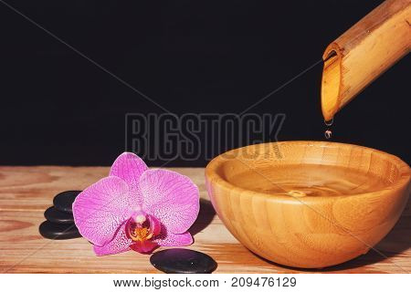 Water Drips From The Bamboo In A Bowl On A Wooden Table, Next To The Spa Treatment Stones And Orchid