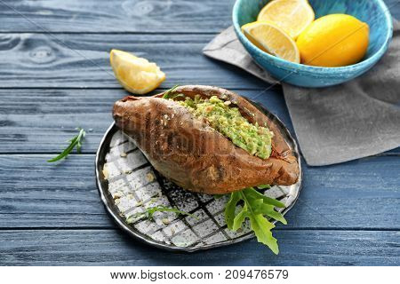 Plate with baked sweet potato and guacamole on wooden table