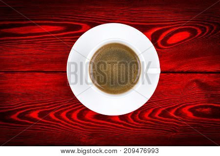 Overhead view of a freshly brewed mug of espresso coffee on red rustic wooden background with woodgrain texture. Coffee break style concept