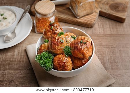 Bowl with delicious meatballs on wooden table