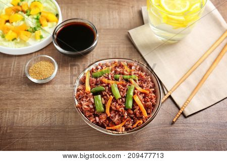 Dish with brown rice on table