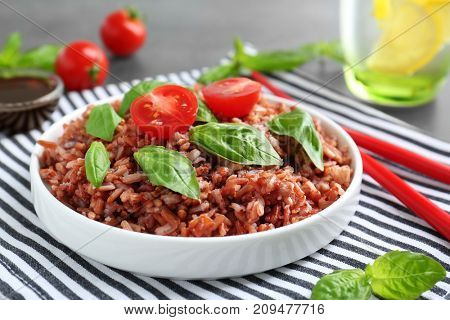 Plate with brown rice on table