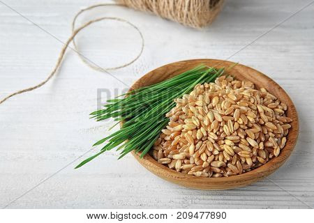 Bowl with wheat grass seeds and sprouts on wooden table