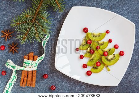 Decorating christmas table New Year's spruce from kiwi. Healthy food on holidays concept.