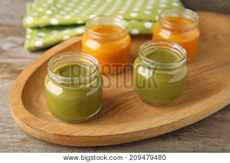 Wooden plate with jars of tasty baby food on table