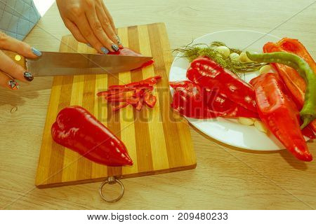 Young Woman Cooking in the kitchen. Healthy Food. Cropped image of young girl cutting vegetables for salad - Retro color