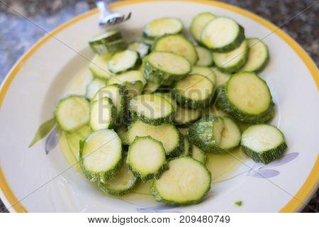 preparing sliced zucchini au gratin with oil and breadcrumb