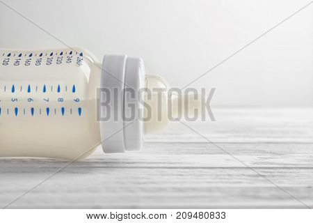 Feeding bottle of baby milk formula on table, close up