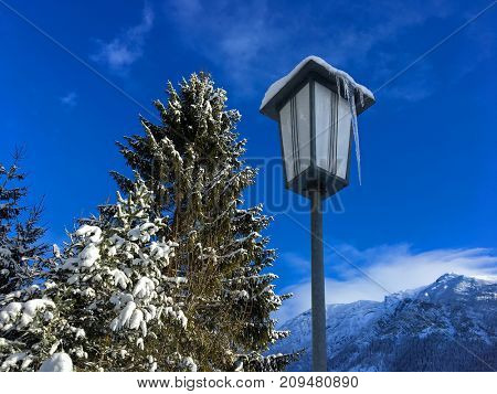Long icicle on street light lamp next to pine tree covered with snow with blurred snowy mountain and blue sky background, winter in Austria, Europe