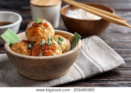 Bowl with delicious meatballs on table