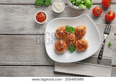 Plate with delicious meatballs and sauces on wooden table