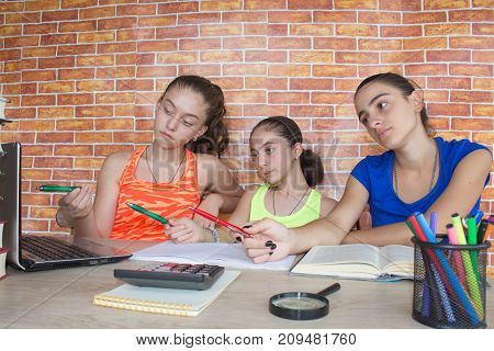 Three Young Girls working on his homework. Thoughts education creativity concept
