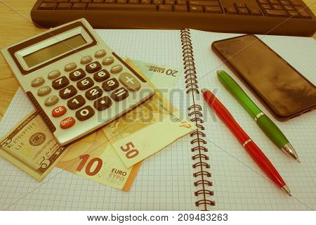 Stock market table analysis calculator and pen indicates research and analysis with cash. analysis of the annual budget with calculator and money on the table. financial concept - Retro color