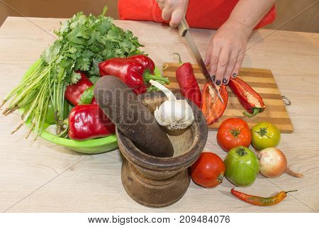 Chef cuts the vegetables into a meal. Preparing dishes. A woman uses a knife and cooks. Woman's hands cutting bell pepper behind fresh vegetables
