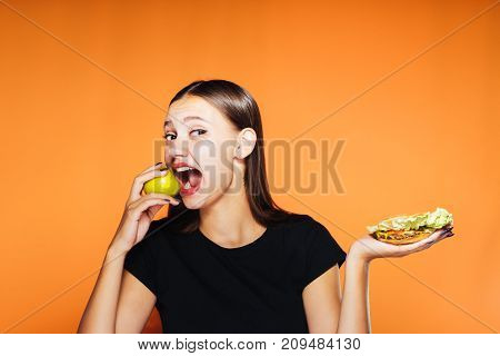 a nice girl chooses that it is better to eat an apple or a mouth-watering sandwich. A girl wants to bite an apple, healthy food, delicious food