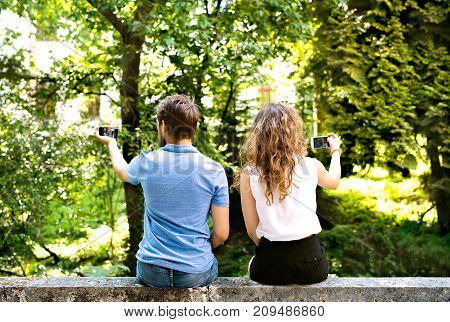 Beautiful young couple with smart phones sitting on concrete wall, taking selfies. Sunny spring day. Rear view.