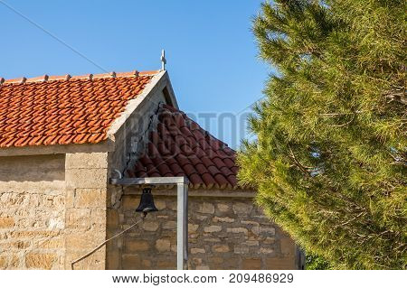 Tiled roof of the church and larch branches against the blue sky.