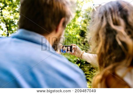 Beautiful young couple with smart phone taking selfie. Sunny spring day. Rear view. Close up.