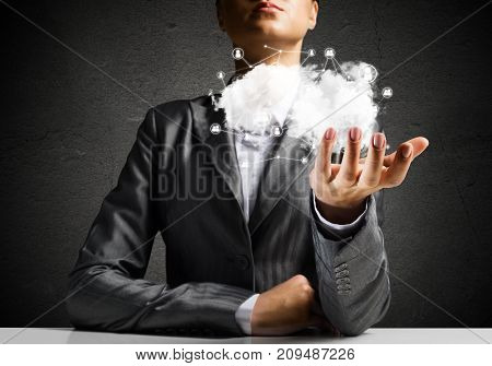Businessman in suit keeping cloud with network connections in hand with gray wall on background.