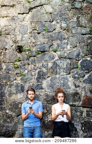 Beautiful young couple with smart phones standing against stone wall in old town, watching or reading something. Sunny spring day.