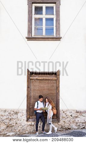 Two beautiful young tourists with map and camera in the old town, next to the wall.
