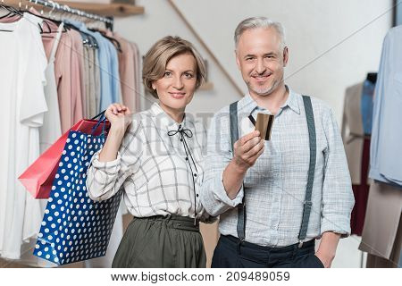 Woman standing with shopping bags and man showing a credit card