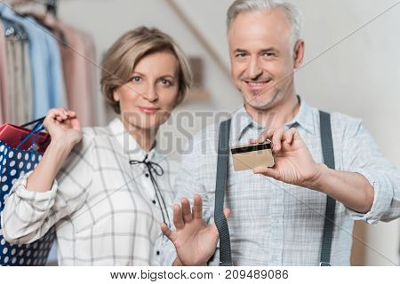 Woman standing with shopping bags and man showing a credit card in a store