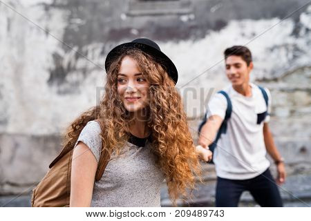Two beautiful young tourists are in love in the old town, holding their hands.