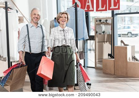 Woman And Man Smiling With Shopping Bags