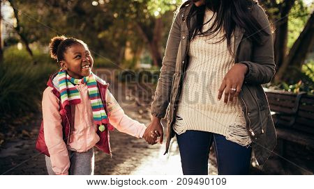 Cute Little Girl With Mother Walking Outdoors