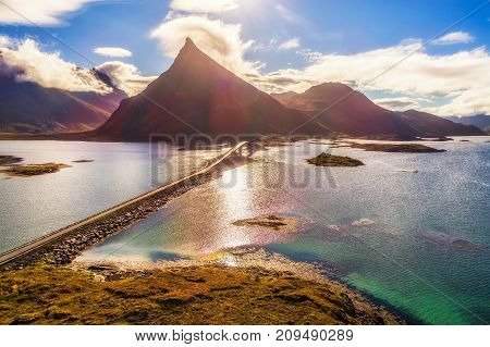 Aerial view of a scenic coastal road with a bridge on Lofoten islands in Norway on a sunny autumn day. HDR processed.
