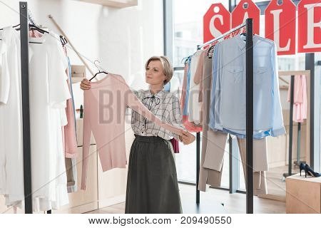 Woman Looking At Pink Shirt