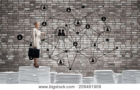 Business woman in suit standing on pile of documents and looking at watch with social network structure on background. Mixed media.