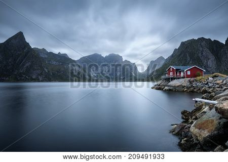Traditional red rorbu cottage under the  mount Olstind in Hamnoy village, Lofoten islands, Norway. Long exposure.