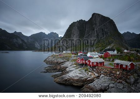 Traditional red rorbu cottages under the  Lilandstinden mountain peak in Hamnoy village, Lofoten islands, Norway. Long exposure.