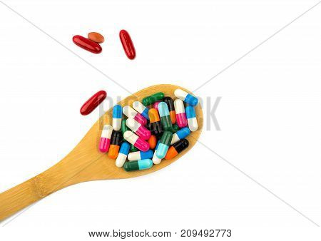 Colorful of capsule pills in wooden spoon are spilling isolated on white background with copy space and clipping path. Antibiotic drug use with reasonable and health insurance concept.