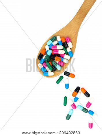 Colorful of antibiotics capsule pills in wooden spoon are spilling isolated on white background with copy space and clipping path. Antibiotic drug use with reasonable and health insurance concept.