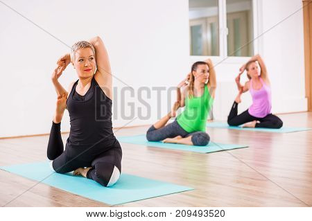 Three girls practicing yoga, Eka pada Rajakapotasana / Pigeon pose