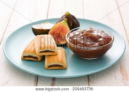 Sweet fig jam smeared on a toast on white wooden table