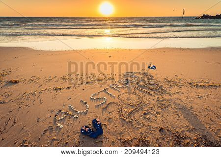Australia 2018 text with thongs flag and sunglasses on beach at sunset