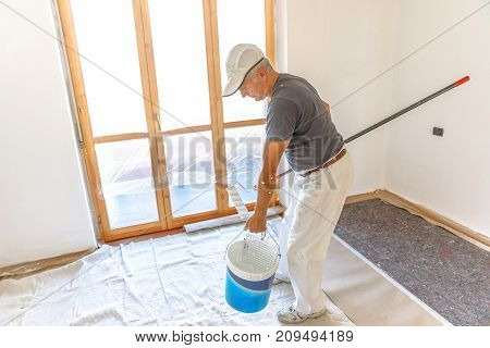 Painter with paint roller and bucket in empty white room for dyeing in white.